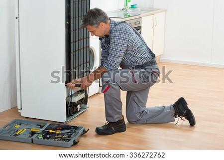 Full length of mature handyman repairing refrigerator at home - stock photo