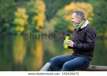 Full length of mature man with thermos while sitting on fence against lake - stock photo