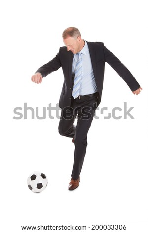 Full length of mid adult businessman kicking soccer ball isolated over white background - stock photo
