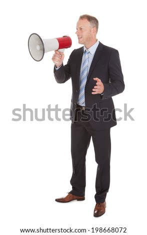 Full length of mid adult businessman using bullhorn over white background