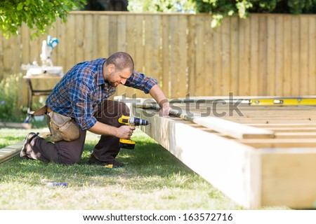 Full length of mid adult carpenter drilling wood at construction site - stock photo