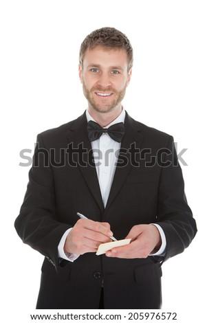 Full length of mid adult waiter writing on notepad over white background - stock photo