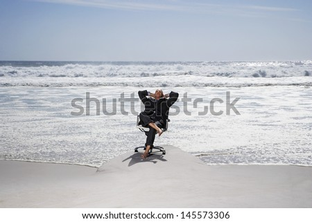 Full length of middle aged businessman relaxing on office chair at beach - stock photo