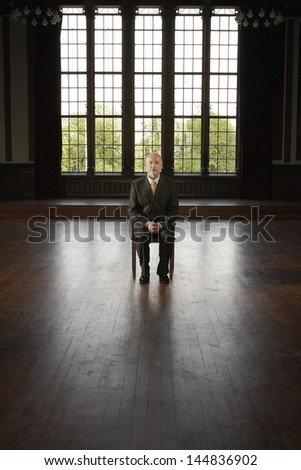 Full length of middle aged businessman sitting on chair in an empty room - stock photo