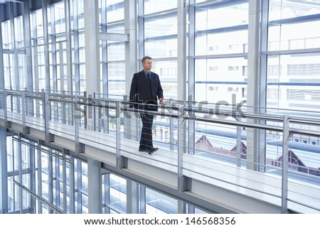 Full length of middle aged businessman walking by railing in modern office - stock photo
