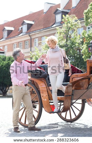 Full-length of middle-aged man assisting woman out of horse cart - stock photo