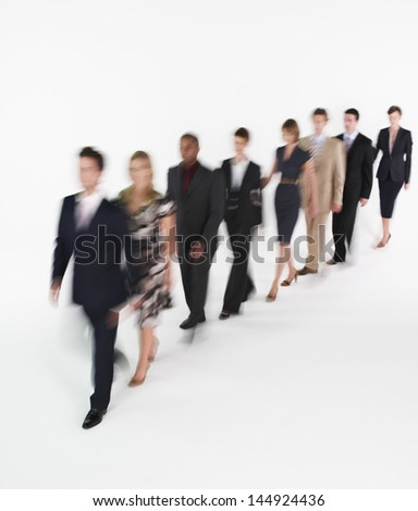 Full length of multiethnic businesspeople walking in blurred motion against white background