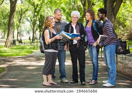 Full length of multiethnic students discussing notes on campus road