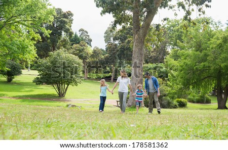 Full length of parents and kids walking in the park - stock photo