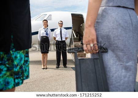 Full length of pilot and airhostess standing near private jet with business people in foreground - stock photo