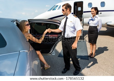 Full length of pilot helping elegant woman stepping out of car at airport terminal - stock photo