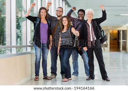 Full length of portrait of multiethnic university students cheering in corridor with professor - stock photo
