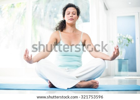 Full length of pregnant woman doing yoga with eyes closed on exercise mat at home - stock photo