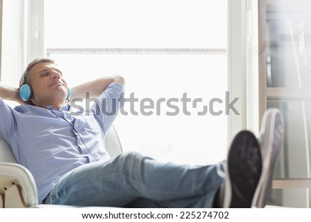 Full-length of relaxed Middle-aged man listening to music at home - stock photo