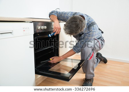 Full length of repairman examining oven with flashlight in kitchen - stock photo
