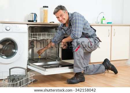 Full length of repairman repairing dishwasher with screwdriver in kitchen