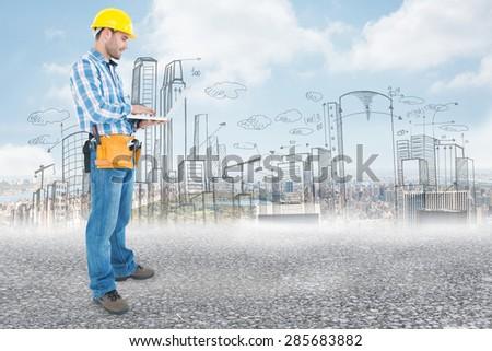 Full length of repairman using laptop against black road - stock photo