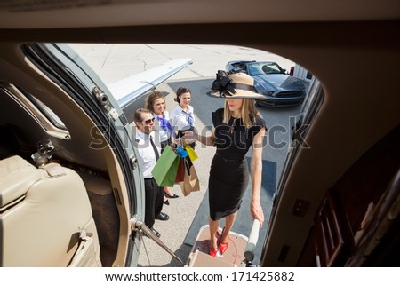 Full length of rich woman with shopping bags boarding private jet while pilot and airhostess looking at her - stock photo