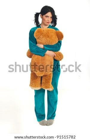 Full length of sad woman in pajamas holding big teddy bear isolated on white background - stock photo