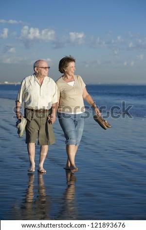 Full length of senior Caucasian couple walking together on beach - stock photo