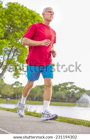 Full length of senior man jogging on footpath by lake