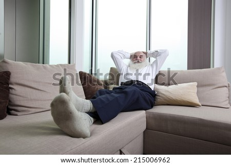 Full length of senior man reclining on sofa with hands behind head at home