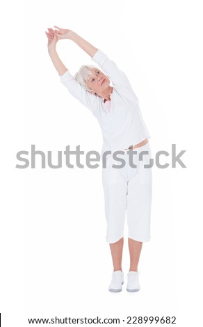 Full length of senior woman doing stretching exercise over white background - stock photo