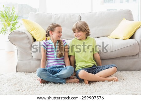 Full length of siblings looking at each other while sitting in liviung room - stock photo