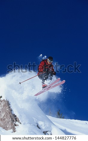 Full length of skier jumping from mountain ledge with deep blue sky in background - stock photo