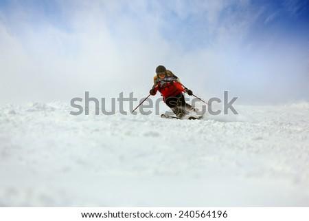 Full length of skier skiing on fresh powder snow - stock photo
