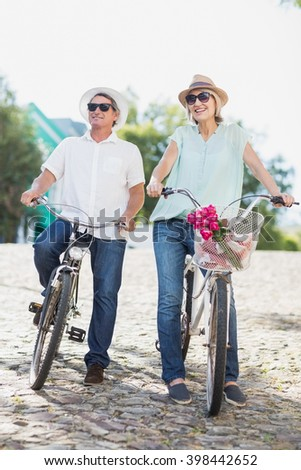 Full length of smiling couple with bicycles on road in city - stock photo