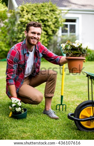Full length of smiling gardener holding potted plants in yard