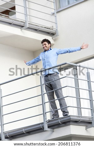 Full length of smiling young businessman standing arms outstretched at hotel balcony - stock photo