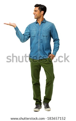 Full length of smiling young man holding invisible product over white background. Vertical shot. - stock photo