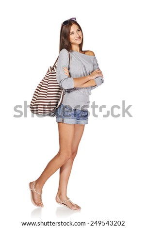 Full length of smiling young slim tanned female in denim shorts with backpack and sunglasses looking away at blank copy space, isolated on white background - stock photo
