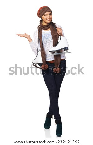 Full length of smiling young woman carrying a pair of ice skates inviting you to skating-rink, over white background - stock photo