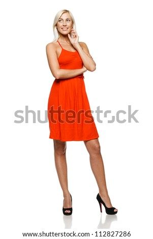Full length of smiling young woman standing with her hands folded looking to the side against white background - stock photo