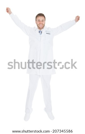 Full length of successful young male doctor with arms raised over white background - stock photo