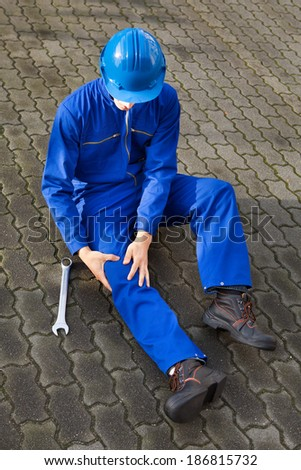 Full length of technician suffering from knee pain while sitting on street - stock photo