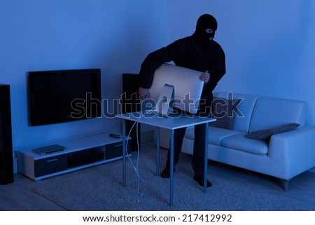 Full length of thief stealing computer monitor from living room - stock photo