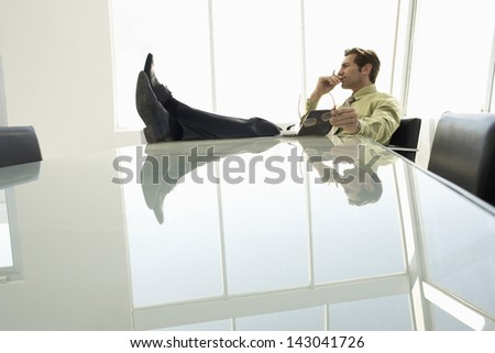 Full length of thoughtful businessman with diary in conference room - stock photo