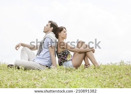 Full length of thoughtful young couple sitting back to back in park - stock photo