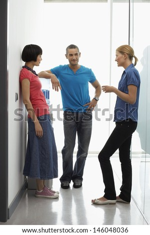 Full length of three office workers talking by water cooler in hallway - stock photo