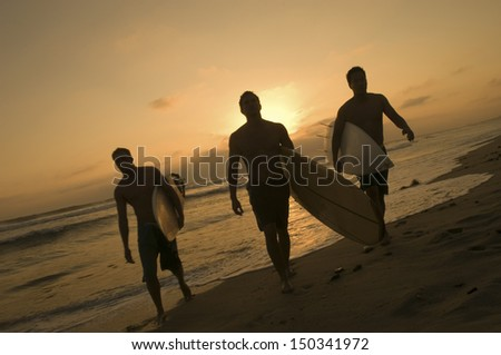 Full length of three surfers carrying surfboards out of surf at sunset - stock photo