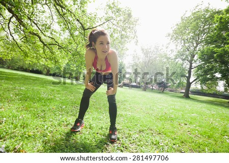 Full length of tired fit woman taking break while exercising in park - stock photo