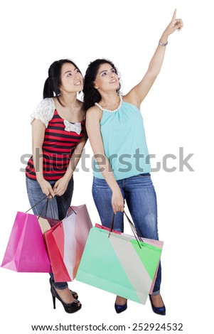 Full length of two asian girl standing in the studio while carrying shopping bags and looking at copyspace - stock photo