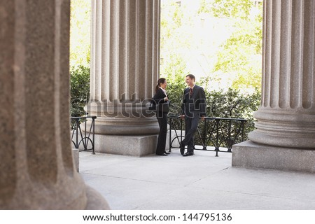 Full length of two attorneys talking outside courthouse - stock photo