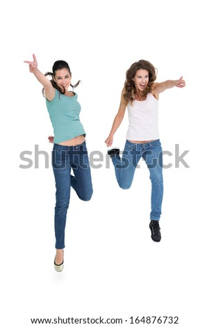 Full length of two cheerful young female friends with hand gestures over white background