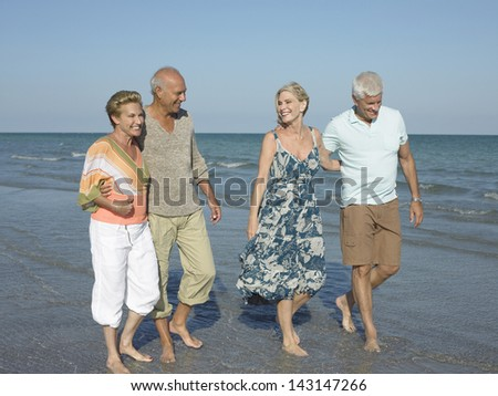 Full length of two couples walking together on tropical beach - stock photo