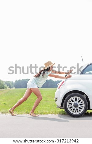 Full-length of woman pushing broken down car on country road - stock photo